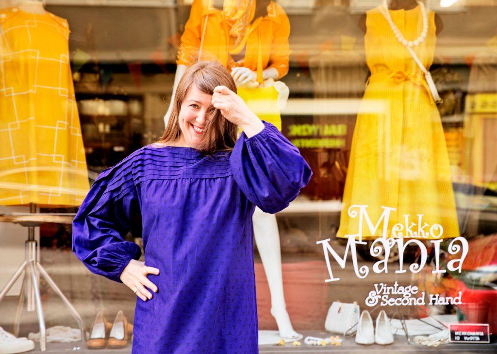 Mekkomanian myyjä seisoo vintage-liikeen edessä ja hymyilee.